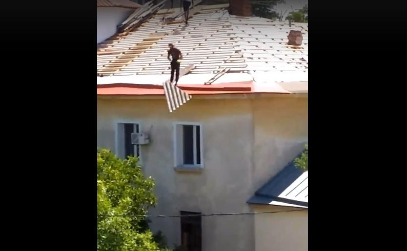 Он не попал: в Севастополе работники скидывают шифер с крыши